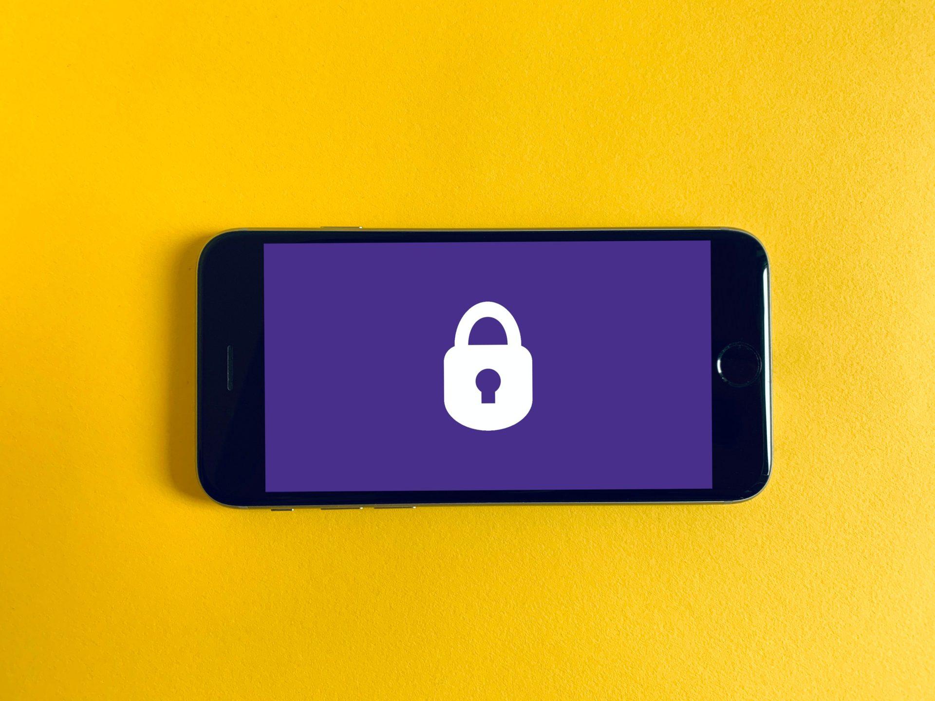smartphone con sfondo giallo e luchetto bianco su sfondo viola
